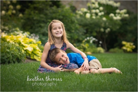 siblings laying in the grass laughing at the camera in montgomery county