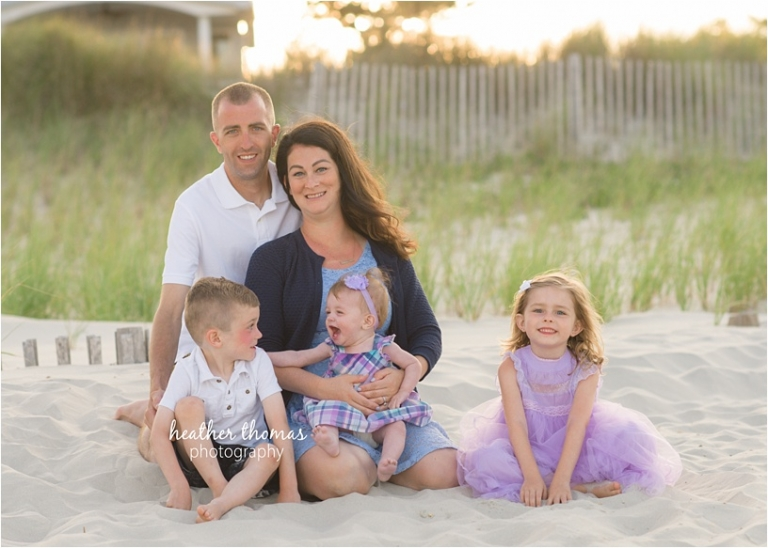 a family of 5 at the beach dressed in purple and navy playing on the beach at sunset in sea isle city, nj
