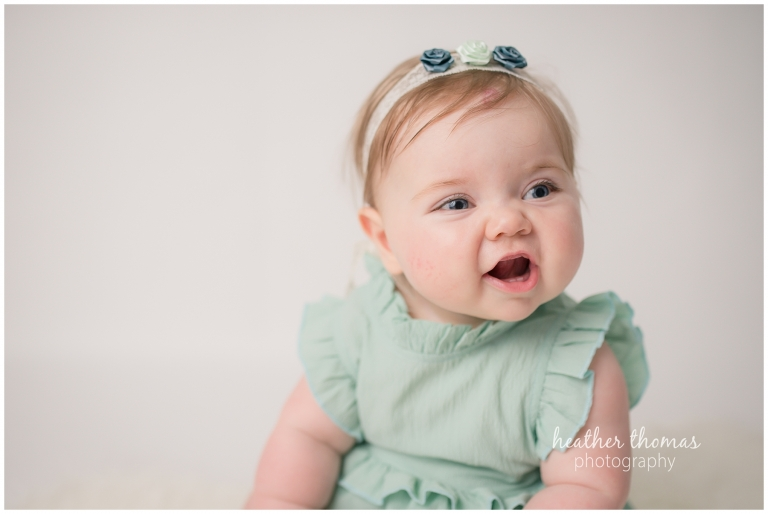 a 6 month old baby wearing teal smiling for camera