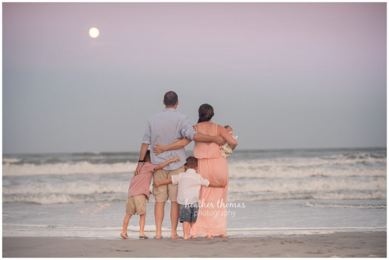 a family of 5 hugging while looking out at the ocean in ocean city nj