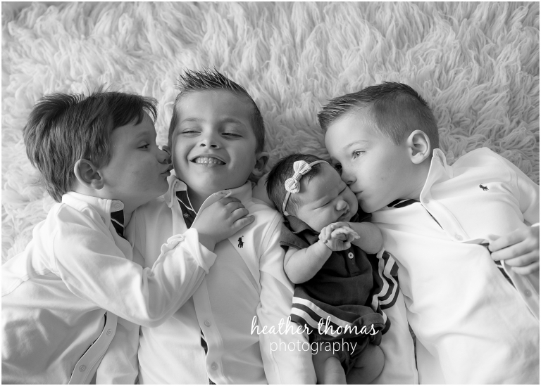 a picture of three boys and a newborn girl laying on a rug in langhorne pa for a photo shoot with heather thomas photography