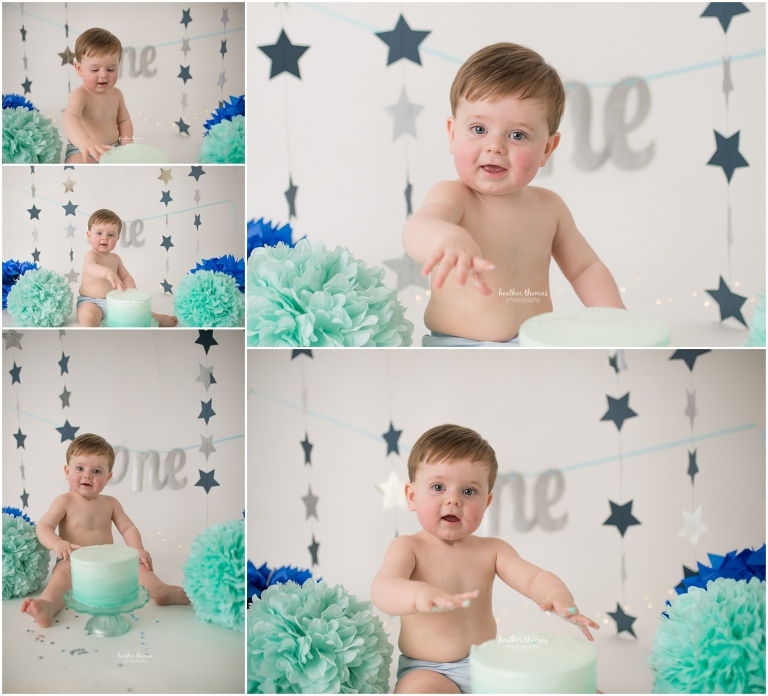 a picture of a one year old boy smiling with his cake at a photo shoot with heather thomas photography