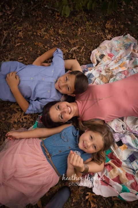 mom and kids smiling on a blanket outside