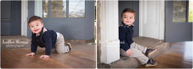 baby boy in a navy blue sweater outside a farmhouse door posing for first birthday portraits in philadelphia photo by heather thomas photography