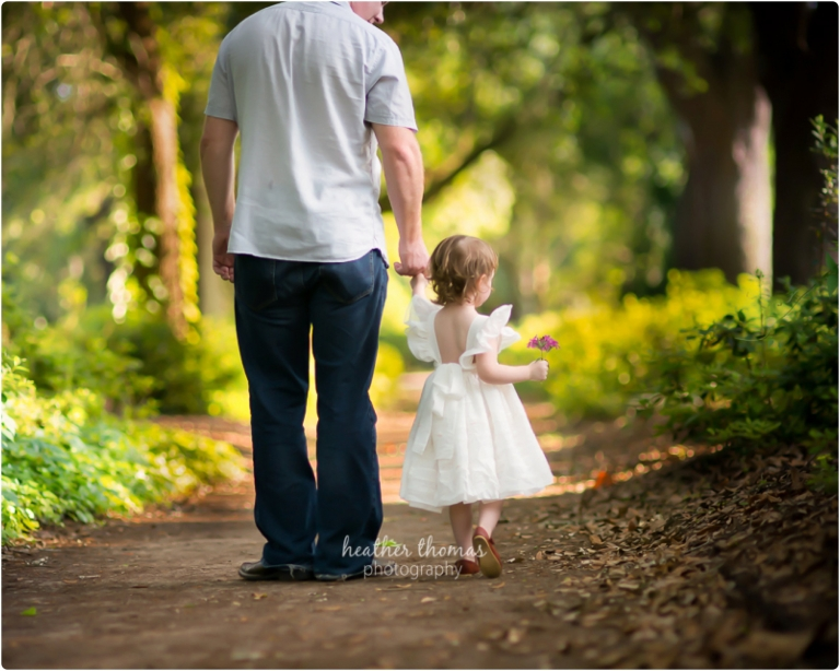 dad and toddler daughter walking in park photo by heather thomas photography