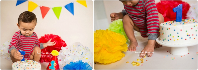 boy in striped shirt enjoying cake for his first birthday