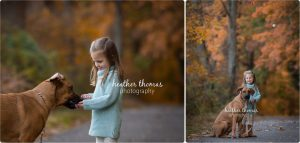 girl in the fall sitting outside playing with her brown boxer at a park in bucks county pa