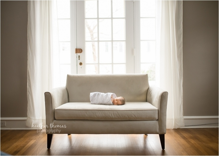 a newborn sitting on a bench in a home