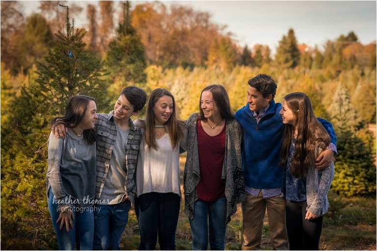 6 teenage cousins laughing at each at the christmas tree farm in yardley pa