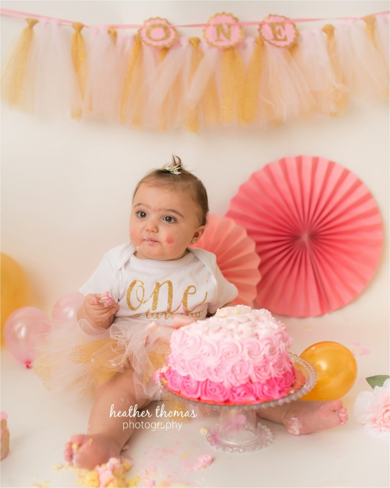 a picture of a one year old wearing white at a cake smash photo shoot in newtown pa