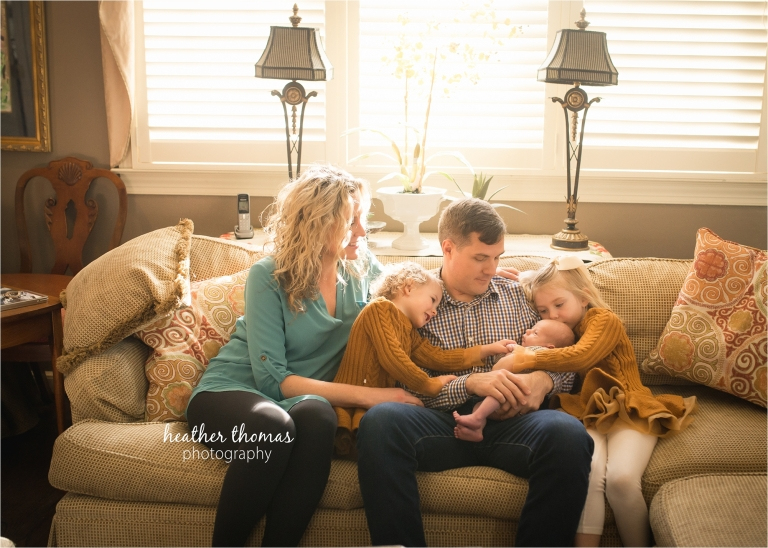 a family cuddling their newborn at their home in chestnut hill with heather thomas photography