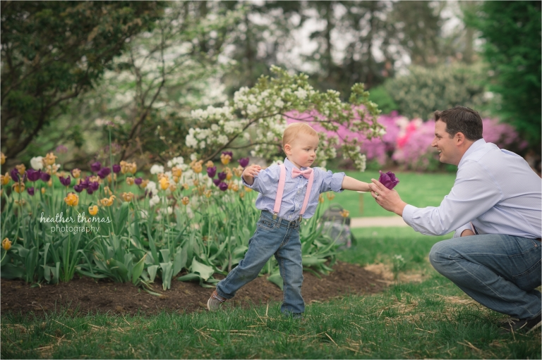 a two year old boy giving a flower to his father at the azalea garden in philadelphia heather thomas photography