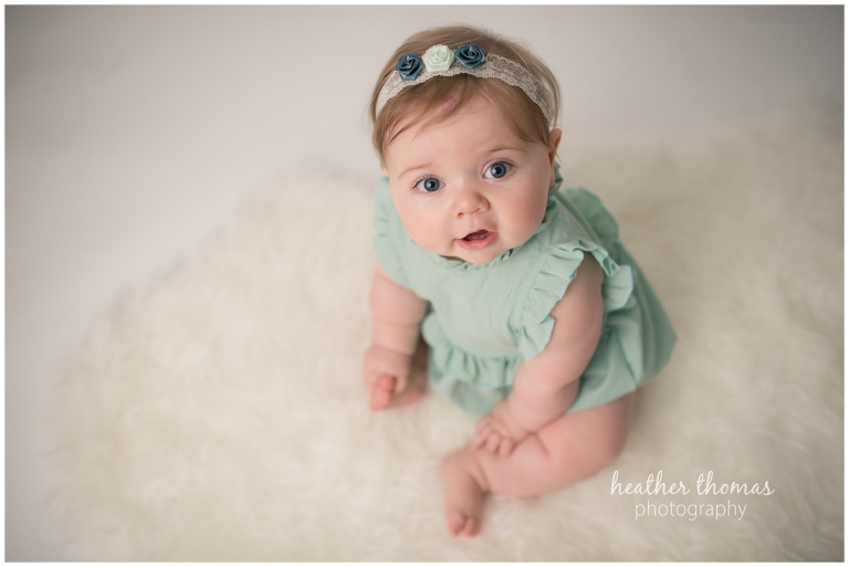a portrait of a 7 month old sitting on a white rug looking up at the camera.