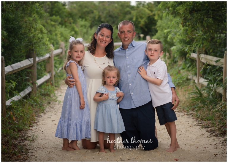 a family of 5 on the beach in sea isle city nj dunes for beach portraits with heather thomas photography