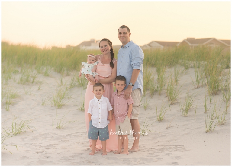 a family of 5 wearing pink white and blue on the dunes in ocean city NJ