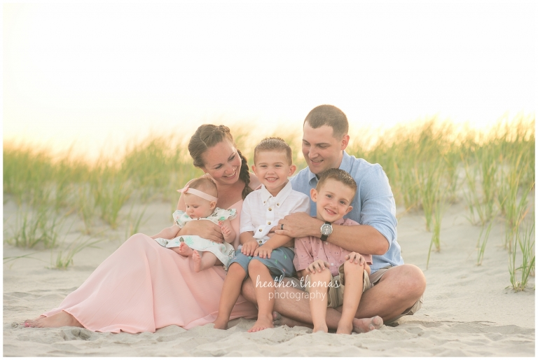 a closeup of a family of 5 wearing pink white and blue on the dunes in ocean city NJ