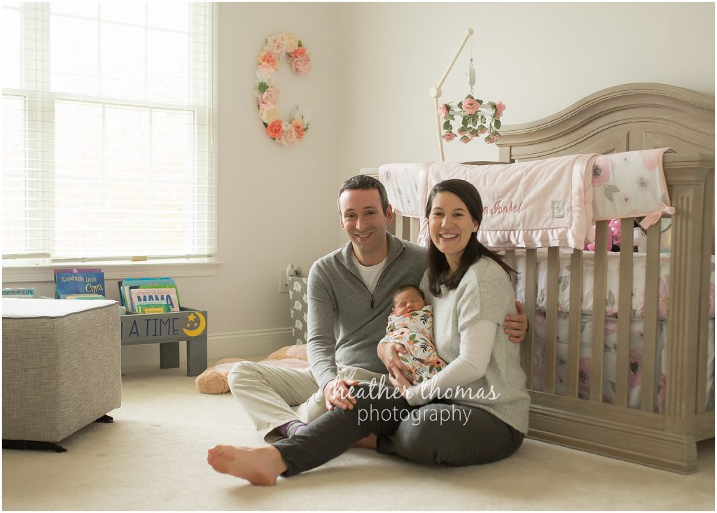 a family holding their newborn in the nursery in their home in newtown pa