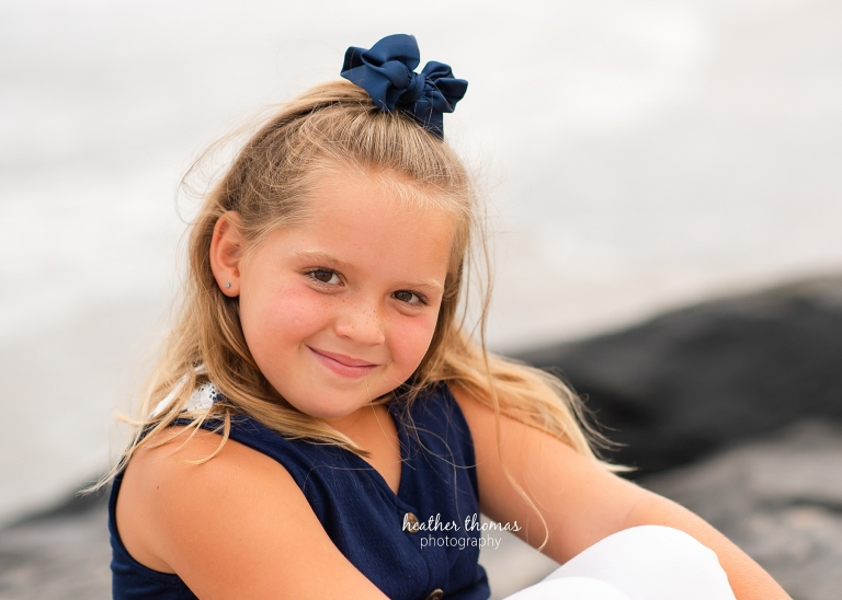 a closeup picture of a girl sitting on the beach in ocean city nj at a photo session with heather thomas photography