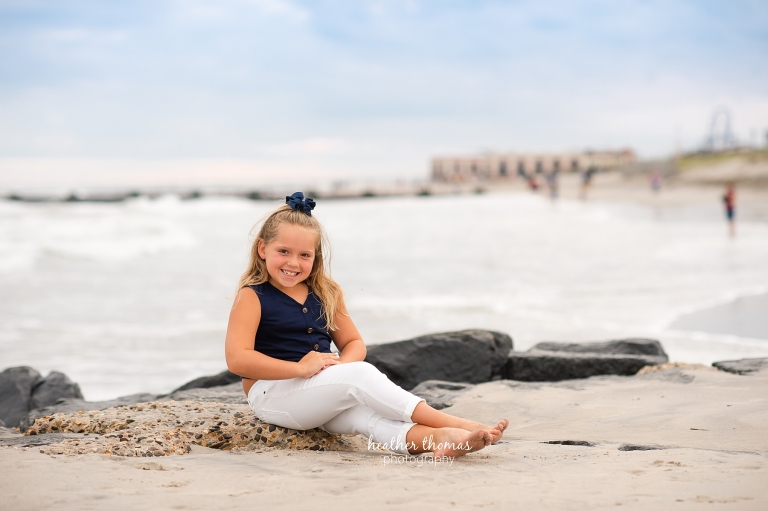 a picture of a girl sitting on the beach in ocean city nj at a photo session with heather thomas photography
