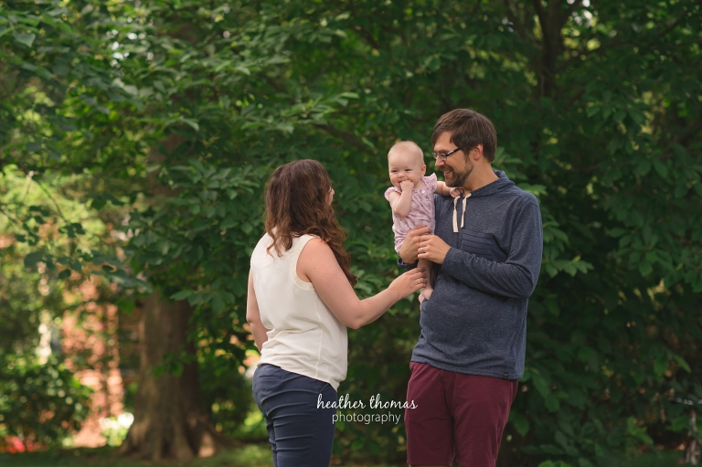 a mom and dad hugging their 6 month old outside for a photo shoot with Heather Thomas Photography in Philadelphia